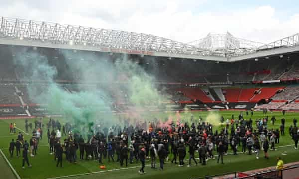 Manchester United fans invade the pitch at Old Trafford ahead of United playing Liverpool.