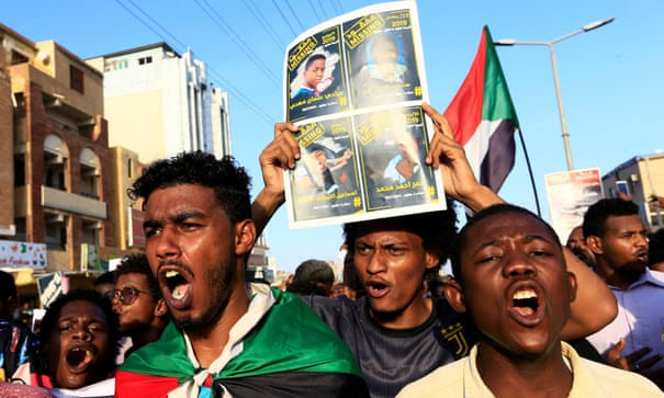 Sudanese protesters hold posters and flags in Khartoum