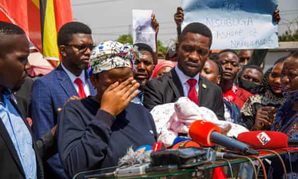 Robert Kyagulanyi with a woman called Halima, whose husband was abducted in December, at press conference in February. Kyagulanyi holds Halima's one-month old baby.