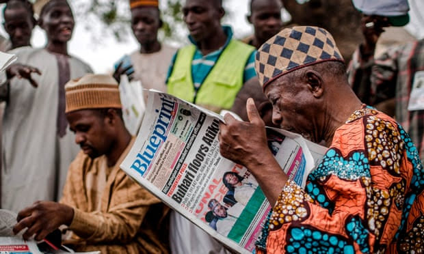 A man reads a national newspaper announcing the victory of Muhammadu Buhari