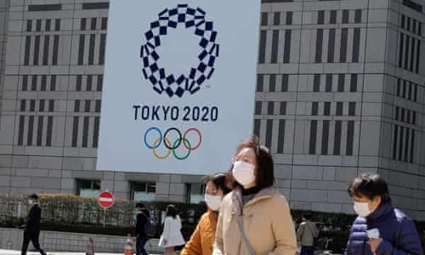 Pedestrians wearing face masks outside the Tokyo Metropolitan Government building, which carries the logo of the 2020 Olympic Games