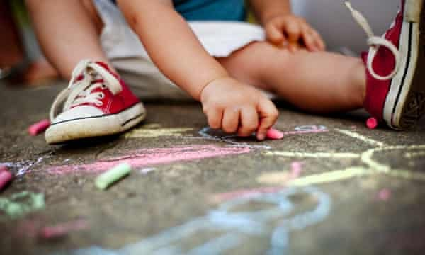 Close-up of boy drawing with chalks