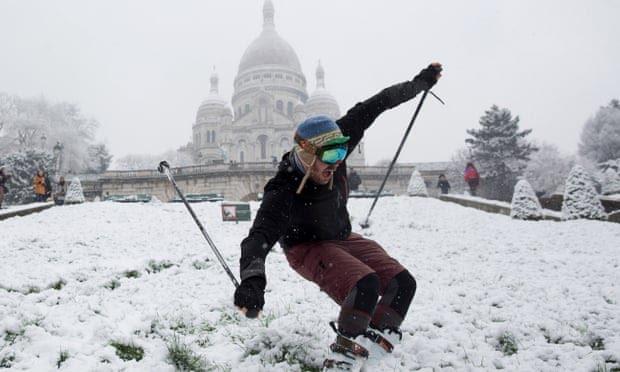 A man skis on Montmartre Hill near Sacré Coeur during a snowfall in Paris.