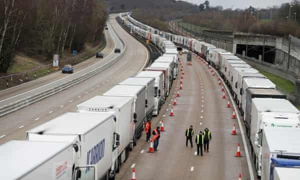 People walk alongside lines of lorries queueing at the M20 motorway near Ashford.