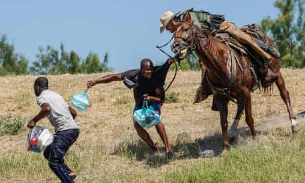 A United States border patrol agent on horseback tries to stop a Haitian migrant from entering an encampment on the banks of the Rio Grande near the international bridge in Del Rio, Texas, on Sunday.
